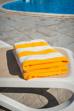 lounger: Yellow towels on sun lounger near the swimming pool. Stock Photo