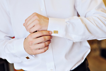 french cuffs: man in a white shirt dress cufflinks. Stock Photo