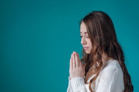 female face: Beautiful woman in white sweater folded her hands in prayer to God. Stock Photo