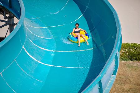 아름 다운 소녀 물 슬라이드를 타고입니다. 스톡 콘텐츠