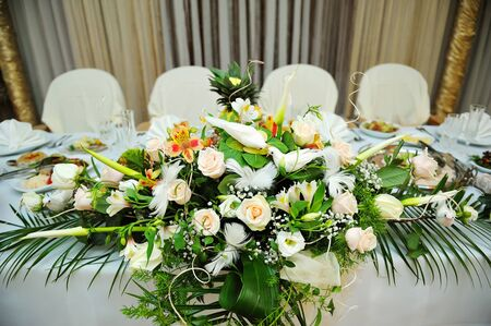 White bouquet of flowers on a festive table bride and groom in a restaurant