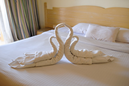 Tucked bed with swans out of towels in a hotel room.