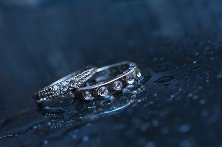anillo de compromiso: dos anillos de boda en un fondo azul. Foto de archivo