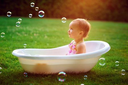 meisje baadt in een bad met zeepbellen. Stockfoto