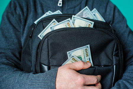 black briefcase: man holding a black briefcase with dollars.