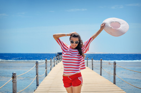 young woman full of energy on a pontoon in front of the sea on a sunny day.