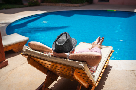 man in a hat lying on a lounger by the pool.