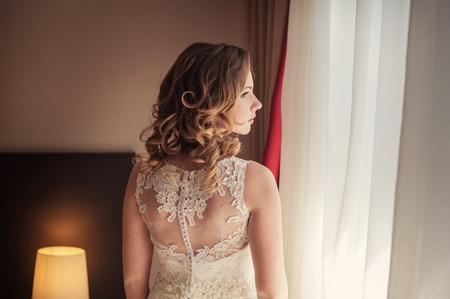 summer dress: Beautiful bride in white wedding dress standing in her bedroom and looking in window