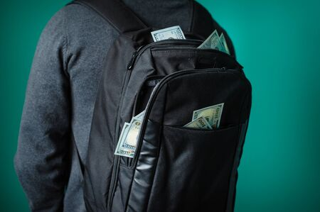 protrude: man with a black backpack from which protrude dollars.