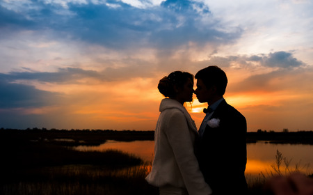 silhouettes of the bride and groom on the background of the setting sun and lake. Foto de archivo
