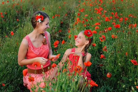 happy families: two girls in red dress on poppy field.