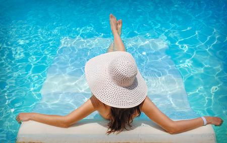 jovem mulher em repouso chapéu branco na piscina.