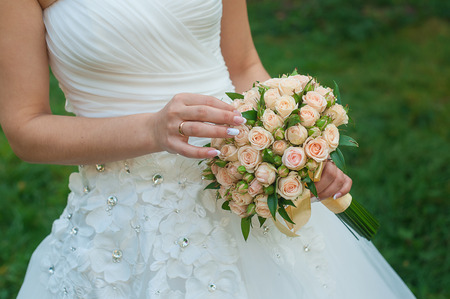 woman red dress: bride holds a beautiful wedding bouquet. Stock Photo