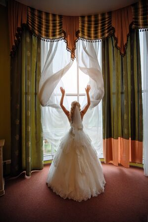 bride dress: bride in a white dress in a hotel room near the window curtains spreads Stock Photo