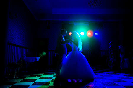 Silhouette of a bride and groom dancing a slow dance in the restaurant.
