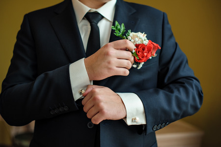 french cuffs: groom in a shirt and tie in the morning wears cufflinks.