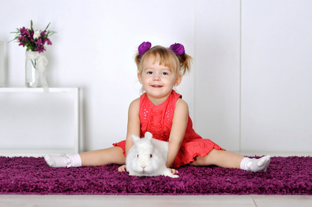Little girl playing with white rabbit.