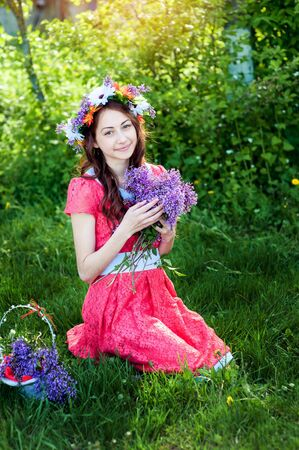 Beautiful woman in red dress sitting on the grass with a branch of lilac.