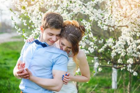 bridegroom: Bride embraces bridegroom in the blossoming spring garden. Stock Photo
