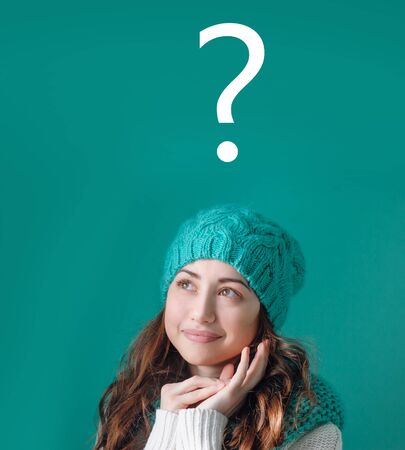 blonde curly hair: thinking women in turquoise knitted hat with question. Stock Photo