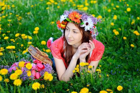 gracefully: Beautiful woman in a red dress lying on a meadow with yellow flowers in spring