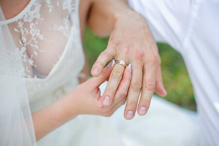 fingers put together: bride wears a gold wedding ring on the finger of the groom. Stock Photo