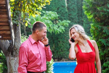 sidewalk talk: Young couple in love walking in the park and talking on the phone. Stock Photo
