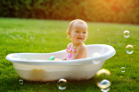 little girl sitting in the bath.