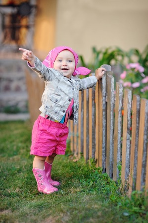 messy clothes: Little girl in pink boots near the fence. Stock Photo