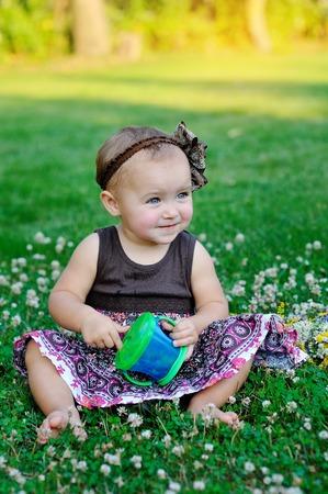 familias felices: linda niña sentada en el césped. Foto de archivo