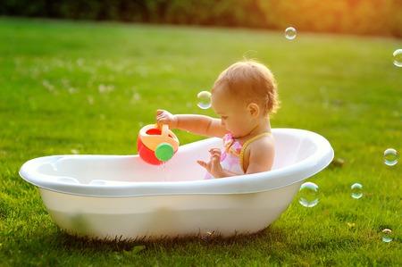 bulles de savon: petite fille assise dans le bain. Banque d'images