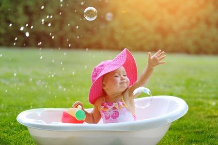 어린 소녀 비누 거품 욕조에 목욕.
