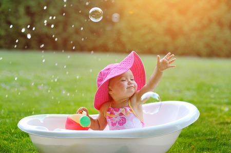 little girl bathes in a bath with soap bubbles. Stockfoto