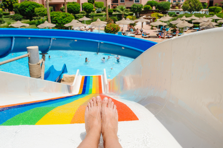 beautiful young woman pulls off the slides in the water park Stock Photo
