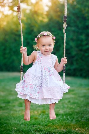chain swing ride: Adorable little girl having fun on a swing.