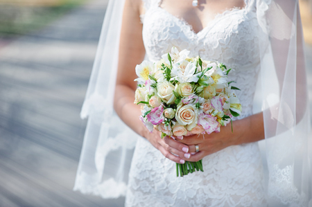 girl with rings: bride holding a wedding bouquet.