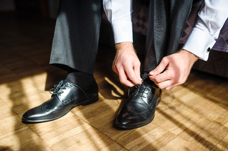 groom: Business man tying shoe laces on the floor. Close-up.