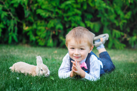 Little boy playing with rabbit on green grass.
