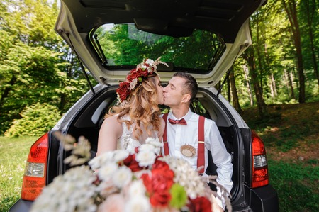white backing: Happy beautiful bride and groom sitting in the trunk of a car and kissing