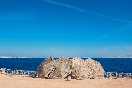 sun umbrellas: wooden sun umbrellas on the beach.