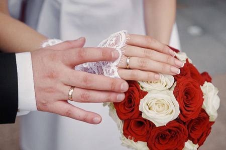 hands with gold rings bride and groom on wedding bouquet.