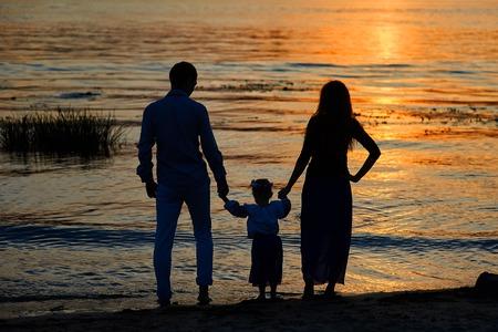 silueta niño: siluetas de los padres y el niño en el fondo de la puesta del sol.