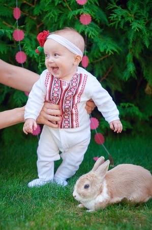 first love: Cute funny happy baby with rabbit making his first steps on a green grass in a sunny summer garden Stock Photo