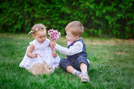 petit bonhomme: Petit garçon donne une fille un bouquet de fleurs. Banque d'images