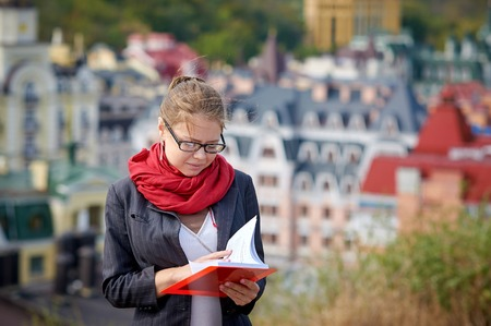 book jacket: Beautiful serious woman in jacket and glasses reads red book against summer buildings.