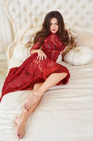 Fashion portrait of elegant young woman in red dress in luxurious interior.