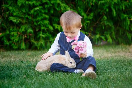 conejo: niño pequeño en un traje de jugar en el parque con un conejo. Foto de archivo