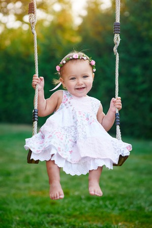 little girl dress: Adorable baby girl wearing a white dress enjoying a swing ride on a playground in a park on a nice sunny summer day