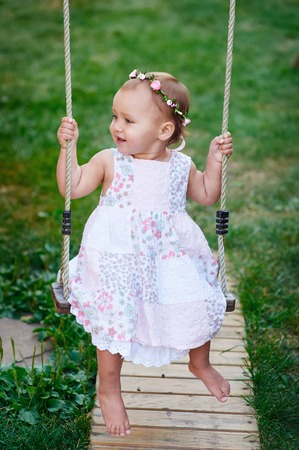 playground ride: Adorable baby girl wearing a white dress enjoying a swing ride on a playground in a park on a nice sunny summer day