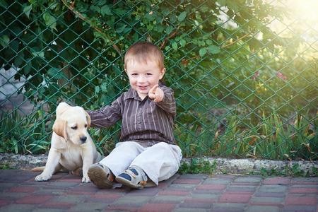 amor adolescente: El niño pequeño juega con un cachorro de labrador blanco.